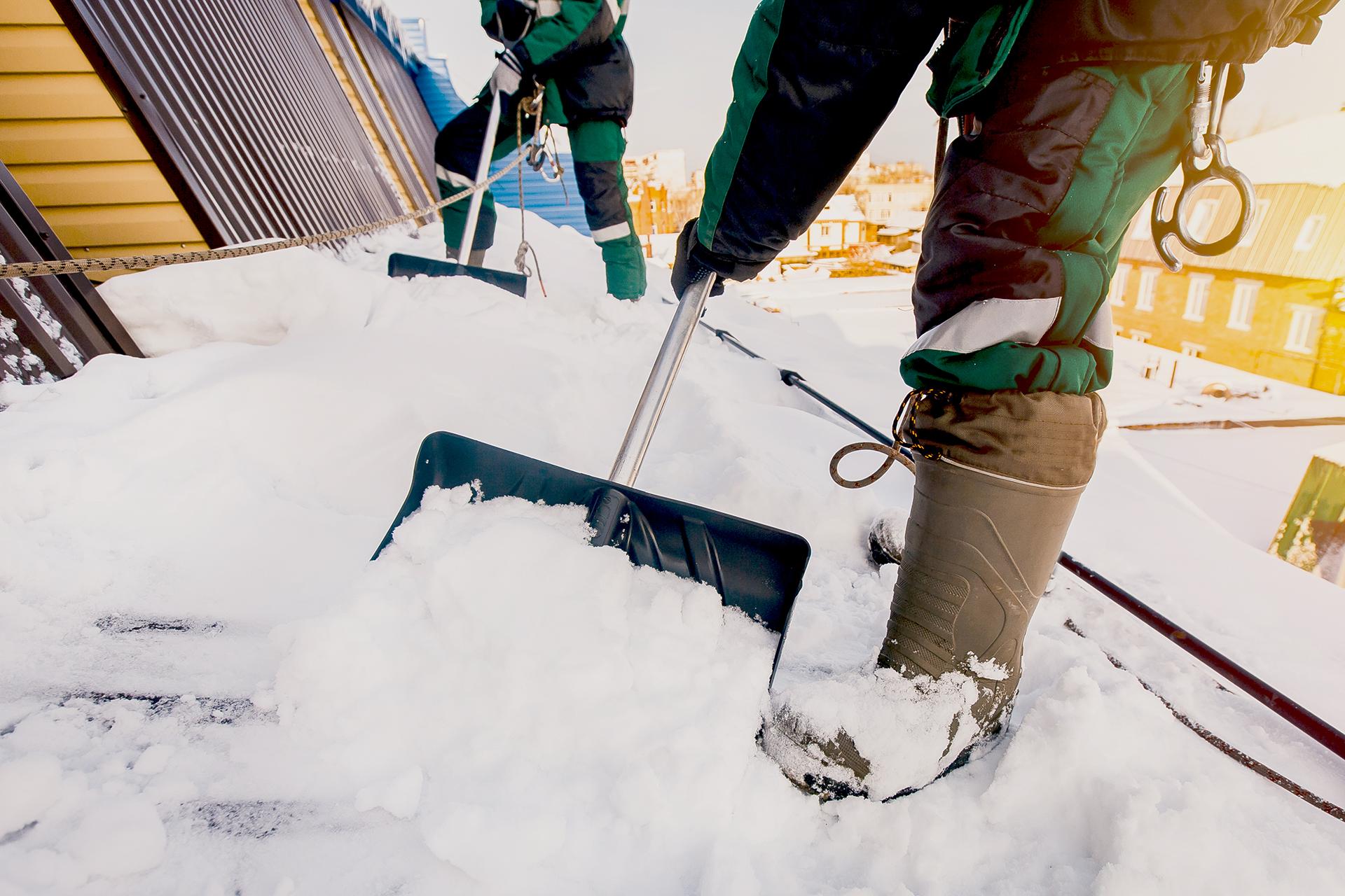 Kiinteistönhuoltaja pudottaa lunta katoilta.